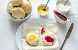 Scones with whipped cream, lemon curd and cranberry jam Stock Images