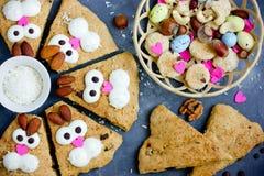 Sconeser för kakor för påskkaninen som dekoreras med kräm och mandlar som roliga kaniner, vänder mot royaltyfri bild