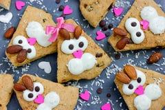 Sconeser för kakor för påskkaninen som dekoreras med kräm och mandlar som roliga kaniner, vänder mot royaltyfri fotografi
