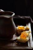 Sconeser med orange marmelad och en tillbringare av mjölkar mot panelljus Royaltyfri Foto