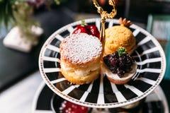 Sconespajtoppning med isläggning och blåbäret Mini Tart på den svartvita plattan efterrätt för eftermiddagte royaltyfri foto