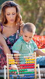 Scool mather son park spring. Mother teaches her son mathematics in the summer park on colorful wooden abacus Stock Photo