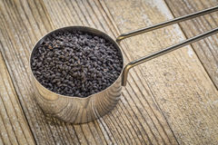 Scoop of black cumin seeds. Black cumin seeds in a metal measuring scoop against grunge wood background Royalty Free Stock Images