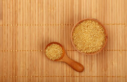 Scoop and bowl of brown cane sugar on mat Stock Photo
