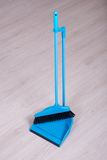 Scoop and broom over wooden floor background Royalty Free Stock Photos