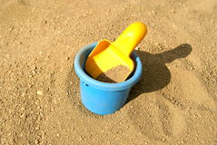 Scoop and bucket on sand. The children's yellow scoop lays in a bucket with sand Stock Photography
