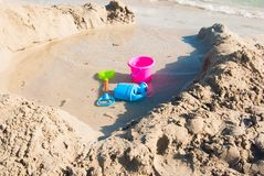 Scoop bucket and watering can on the shoreline royalty free stock photo