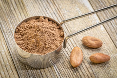 Scoop of cacao powder with beans Royalty Free Stock Photos
