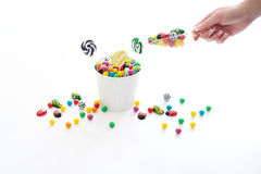 A scoop of candy. Female hand holding a scoop of candy with a bucket full of candy that has spilled over royalty free stock images