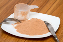 Scoop of chocolate whey protein on a plate Royalty Free Stock Images