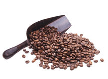 Scoop with coffee beans scattered from it on white Royalty Free Stock Photos