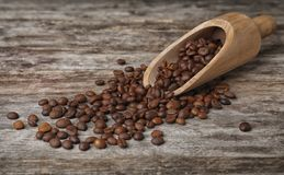 Scoop and coffee beans. On wooden table Royalty Free Stock Image
