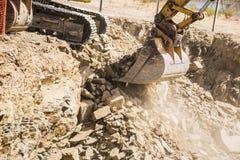 Scoop d'une excavatrice, bêcheur enlevant des roches Photographie stock libre de droits