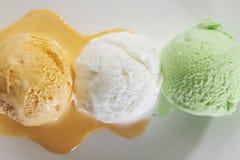 Scoop de vraie crème glacée fraîche délicieuse dans la saveur de mangue, de vanille et de pistache image libre de droits