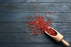 Scoop and dried goji berries on blue wooden table, space for text. Healthy superfood. Scoop and dried goji berries on blue wooden table, top view with space for royalty free stock photography