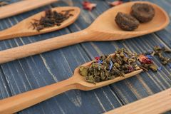 Scoop of dry green tea leaves with flower petals on wooden background royalty free stock images