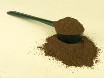 Scoop of fresh ground coffee over pale background Stock Images