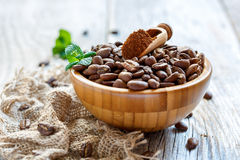 Scoop with ground coffee in a bowl with roasted beans. Royalty Free Stock Photography