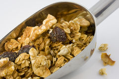 Scoop of healthy, organic granola. Metal scoop full of healthy, organic granola on white background Royalty Free Stock Photo