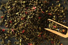 Scoop and heap of dry tea leaves on wooden background, closeup royalty free stock photo