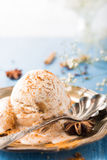 Scoop of homemade ice cream with cinnamon. Apple syrup and spices on metal plate on blue wooden background. Summer food concept. Copy space Royalty Free Stock Photo