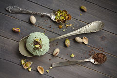 Scoop of homemade pistachio ice cream with chopped pistachios and chocolate. On old wooden backgroung Stock Photo