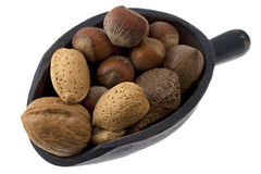 Scoop of mixed nuts. Hazelnuts, almonds, pecans, walnuts and Brazilian nuts on a rustic wooden scoop isolated on white Stock Photo