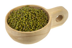 Scoop of mung beans. Mung beans on a primitive, rustic, wooden scoop (bowl), isolated on white Stock Image