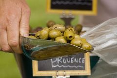 Scoop of olives being put into a bag Stock Photo