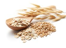 Oats. Scoop and pile of oatmeal with its unprocessed grains and plant Stock Images