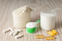 Scoop of protein, bcaa and creatine, omega3 in pills. On wooden background Royalty Free Stock Image