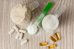 Scoop of protein, bcaa and creatine, omega3 in pills Stock Photos