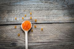 Scoop of red caviar on the wooden background Stock Photo
