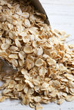 Scoop of Rolled Oats. On weathered timber background Stock Photos