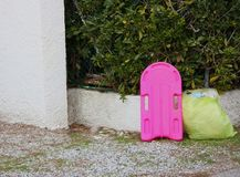 Scoop to learn to swim in a girl`s fuchsia color. end of the summer season. useless object to be trashed. Abandoned on the side of the road along with a yellow royalty free stock photography