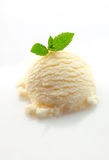 Scoop of vanilla ice-cream and mint Royalty Free Stock Photography