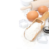 Scoop with wheat flour, rolling pin, eggs, cookie cutters isolated Stock Photos