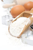 Scoop with wheat flour, rolling pin, eggs and cookie cutters Royalty Free Stock Photo