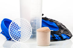 Scoop of whey protein in front of gym equipment royalty free stock images