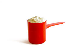 scoop of whey protein in a red spoon. Scoop of whey protein in a red spoon Royalty Free Stock Photography