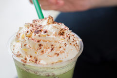 Scoop Whipped Cream on the Green Tea Frappucino. People is scopping whipped cream on the Green Tea Frappucino Stock Photo