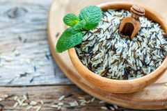 Scoop in a wooden bowl with mixture of wild and white rice. Royalty Free Stock Images