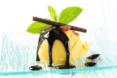 Ice cream with chocolate sauce and mint sticks. Scoop of yellow ice cream topped with chocolate sauce and mint sticks royalty free stock photos
