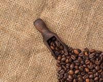Scooper met koffiebonen op juteachtergrond Stock Fotografie