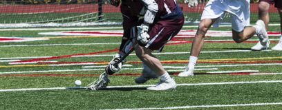 Scooping up a lacrosse ball during a game. A high school lacrosse athlete is scooping up the ball off of the turf during a game stock images