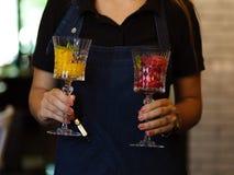Scoops colorés de sorbet avec la menthe dans des mains femelles Deux beaux verres à vin en cristal avec la crème glacée de fruit  Images libres de droits