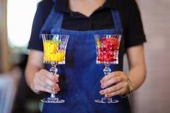 Scoops colorés de sorbet avec la menthe dans des mains femelles Deux beaux verres à vin en cristal avec la crème glacée de fruit  Images stock