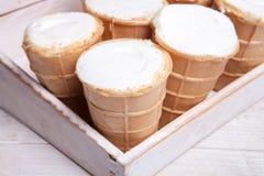 Scoops de crème glacée dans la tasse de gaufre Crème glacée dans une gaufre sur le bois blanc et le fond bleu Crème glacée délici Photographie stock