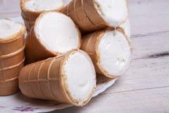 Scoops de crème glacée dans la tasse de gaufre Crème glacée dans une gaufre sur le bois blanc et le fond bleu Crème glacée délici Image libre de droits