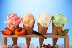 Scoops de crème glacée de différentes couleurs et saveurs avec la décoration de baies, d'écrous et de fruits sur le fond blanc photo libre de droits
